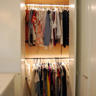 Inspiration for a mid-sized midcentury gender-neutral built-in wardrobe in New York with white cabinets.