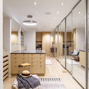 Exempel på ett stort modernt walk-in-closet för könsneutrala, med släta luckor, skåp i ljust trä, ljust trägolv och beiget golv