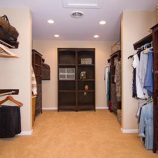 Imagen de armario vestidor exótico, grande, con armarios con paneles empotrados, puertas de armario de madera en tonos medios, moqueta y suelo beige