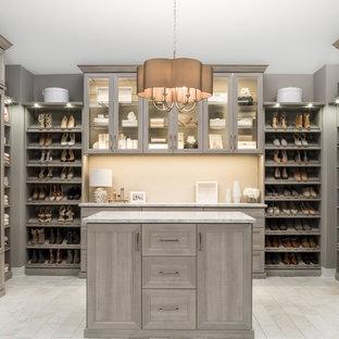 Diseño de armario vestidor unisex, moderno, extra grande, con suelo beige, puertas de armario grises y armarios con paneles empotrados