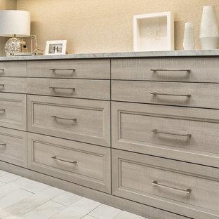 Cette photo montre un très grand dressing moderne neutre avec des portes de placard grises, un placard avec porte à panneau encastré et un sol gris.
