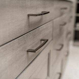 Ejemplo de armario vestidor unisex, moderno, extra grande, con armarios estilo shaker, puertas de armario de madera oscura, suelo de madera clara y suelo beige