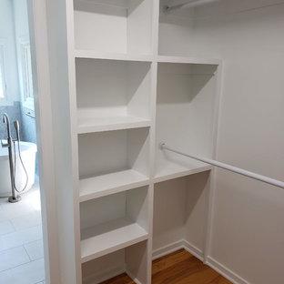 Idéer för mellanstora funkis walk-in-closets för könsneutrala, med öppna hyllor, vita skåp, mellanmörkt trägolv och brunt golv