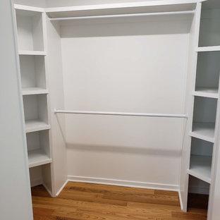 Esempio di una cabina armadio unisex minimal di medie dimensioni con nessun'anta, ante bianche, pavimento in legno massello medio e pavimento marrone