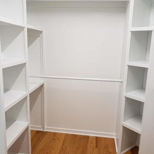 Réalisation d'un dressing design de taille moyenne et neutre avec un placard sans porte, des portes de placard blanches, un sol en bois brun et un sol marron.