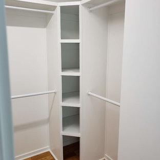 Diseño de armario vestidor unisex, actual, de tamaño medio, con armarios abiertos, puertas de armario blancas, suelo de madera en tonos medios y suelo marrón