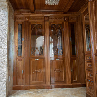 Inspiration for a large traditional gender neutral walk-in wardrobe in San Diego with medium wood cabinets and travertine flooring.