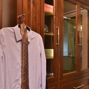 Modelo de vestidor de hombre, tradicional renovado, grande, con armarios tipo vitrina, puertas de armario de madera oscura y suelo de madera oscura