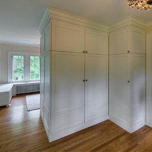 Diseño de vestidor unisex, romántico, con armarios estilo shaker, puertas de armario blancas y suelo de madera en tonos medios