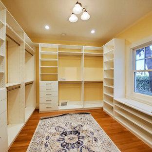 Immagine di una cabina armadio unisex di medie dimensioni con ante lisce, ante bianche, pavimento in legno massello medio e pavimento marrone