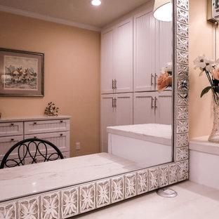 Foto de vestidor de mujer, tradicional renovado, de tamaño medio, con armarios con rebordes decorativos, puertas de armario blancas, suelo de madera oscura y suelo marrón