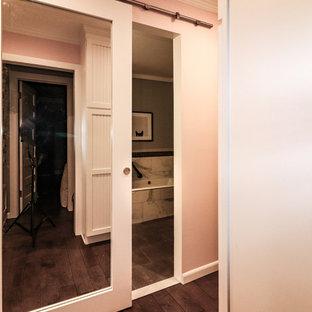Modelo de vestidor de mujer, tradicional renovado, de tamaño medio, con armarios con rebordes decorativos, puertas de armario blancas, suelo de madera oscura y suelo marrón