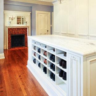 Modelo de vestidor unisex, clásico, extra grande, con armarios con rebordes decorativos, puertas de armario blancas y suelo de madera en tonos medios
