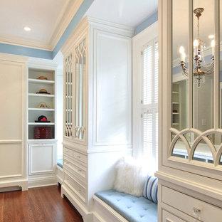 Exemple d'un dressing room chic neutre avec un placard à porte affleurante, des portes de placard blanches et un sol en bois brun.