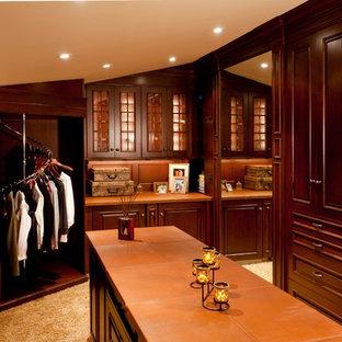 Imagen de vestidor unisex, clásico, extra grande, con armarios con paneles con relieve, puertas de armario de madera en tonos medios y moqueta