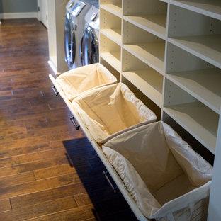 アトランタの広い男女兼用トランジショナルスタイルのおしゃれなウォークインクローゼット (レイズドパネル扉のキャビネット、白いキャビネット、無垢フローリング、茶色い床) の写真