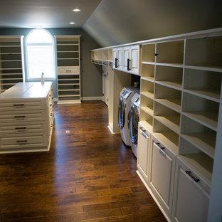 Klassisk inredning av ett stort walk-in-closet för könsneutrala, med luckor med upphöjd panel, vita skåp, mellanmörkt trägolv och brunt golv