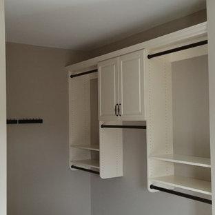 Ejemplo de armario vestidor de mujer, clásico, de tamaño medio, con armarios con paneles con relieve, puertas de armario blancas, moqueta y suelo beige