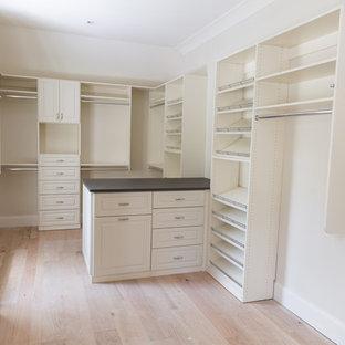 Imagen de armario vestidor unisex, tradicional renovado, grande, con armarios con paneles con relieve, puertas de armario blancas y suelo de madera clara
