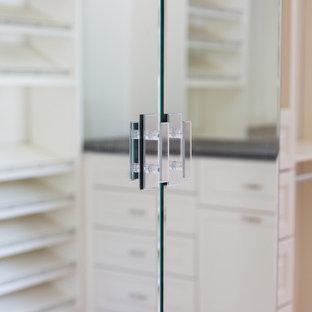 Imagen de armario vestidor unisex, de estilo americano, grande, con armarios con paneles con relieve, puertas de armario blancas y suelo de madera clara