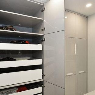 Foto de vestidor unisex, actual, grande, con armarios con paneles lisos, puertas de armario grises y suelo de baldosas de cerámica