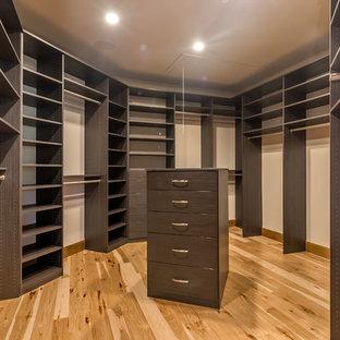 Diseño de armario vestidor unisex, mediterráneo, extra grande, con armarios con paneles lisos, puertas de armario de madera en tonos medios y suelo de madera clara