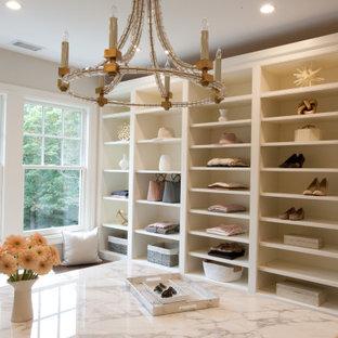 Modelo de armario vestidor de mujer y abovedado, clásico renovado, grande, con armarios con rebordes decorativos, puertas de armario blancas, suelo de madera oscura y suelo marrón