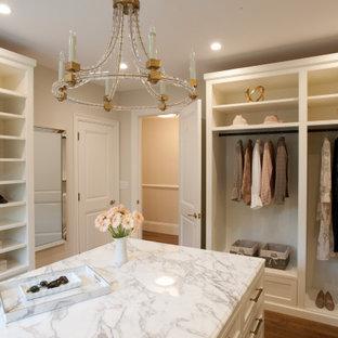 Ejemplo de armario vestidor de mujer y abovedado, tradicional renovado, grande, con armarios con rebordes decorativos, puertas de armario blancas, suelo de madera oscura y suelo marrón