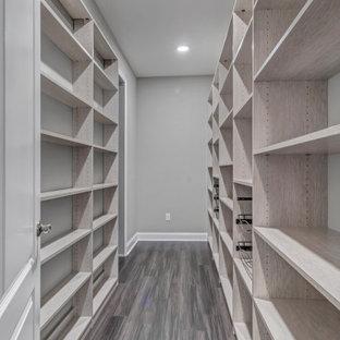 Ejemplo de armario vestidor mediterráneo, grande, con armarios con paneles lisos, puertas de armario de madera oscura, suelo vinílico y suelo marrón