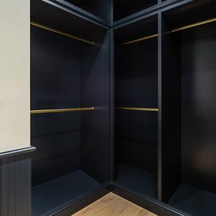 Foto de armario vestidor de hombre, minimalista, de tamaño medio, con armarios abiertos, puertas de armario blancas y suelo de madera en tonos medios