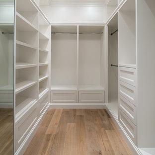 Ejemplo de armario vestidor de mujer, clásico, de tamaño medio, con armarios abiertos, puertas de armario blancas y suelo de madera en tonos medios