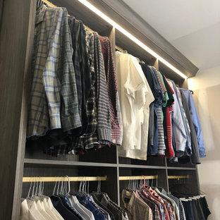 Großer Moderner Begehbarer Kleiderschrank mit flächenbündigen Schrankfronten, grauen Schränken, Teppichboden und blauem Boden in New York