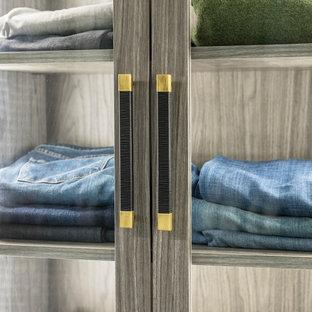 Diseño de armario vestidor de hombre, moderno, grande, con armarios con paneles lisos, puertas de armario grises, moqueta y suelo azul
