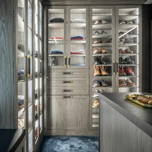 Cette image montre un grand dressing design pour un homme avec des portes de placard grises, moquette, un sol bleu et un placard à porte vitrée.