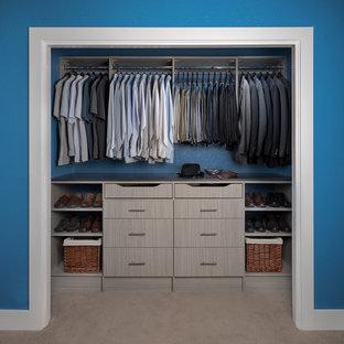 Cette image montre un placard dressing design de taille moyenne pour un homme avec un placard à porte plane, des portes de placard en bois clair, moquette et un sol beige.