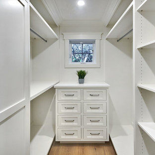 Inspiration for a small farmhouse gender-neutral light wood floor and gray floor walk-in closet remodel in San Francisco with shaker cabinets and white cabinets