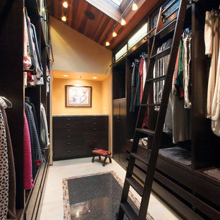 This is an example of a contemporary gender neutral walk-in wardrobe in Seattle with dark wood cabinets and travertine flooring.