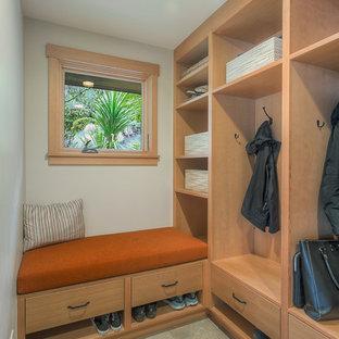Modelo de armario y vestidor tradicional renovado, de tamaño medio, con armarios con paneles lisos, puertas de armario de madera clara, suelo de pizarra y suelo gris
