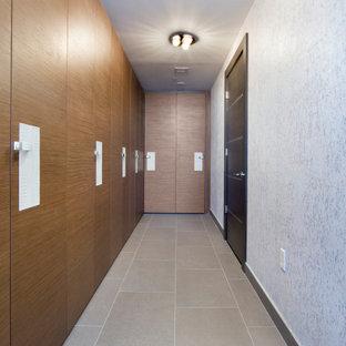 Diseño de armario y vestidor unisex, moderno, grande, con armarios con paneles lisos, puertas de armario de madera oscura, suelo de baldosas de porcelana y suelo gris