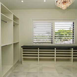 Idee per un grande spazio per vestirsi unisex minimalista con nessun'anta, ante bianche, pavimento in marmo e pavimento bianco