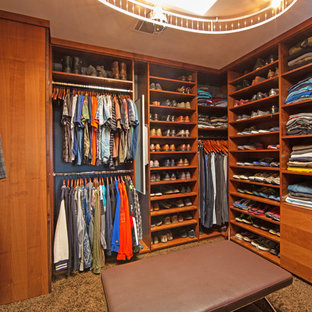 Photo of a large midcentury gender-neutral dressing room in San Diego with flat-panel cabinets, medium wood cabinets and carpet.