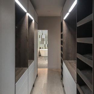 Mittelgroßer Mid-Century Begehbarer Kleiderschrank mit flächenbündigen Schrankfronten, dunklen Holzschränken und hellem Holzboden in Toronto