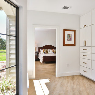 Photo of a mid-sized midcentury gender-neutral walk-in wardrobe in Austin with flat-panel cabinets, white cabinets, light hardwood floors and beige floor.