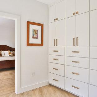 Modelo de armario vestidor unisex, vintage, de tamaño medio, con armarios con paneles lisos, puertas de armario blancas, suelo de madera clara y suelo beige