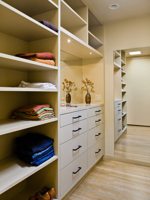 Example of a large minimalist light wood floor walk-in closet design in San  Francisco