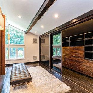 Inspiration pour un très grand dressing room vintage pour un homme avec un placard à porte plane, des portes de placard en bois brun, sol en stratifié et un sol marron.
