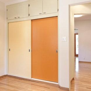 Imagen de armario unisex, moderno, pequeño, con armarios con paneles lisos, puertas de armario naranjas y suelo de madera clara