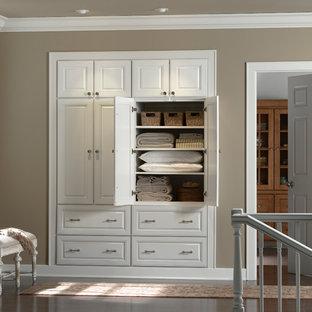 Foto de armario clásico, de tamaño medio, con armarios con paneles con relieve, puertas de armario blancas, suelo de madera oscura y suelo marrón