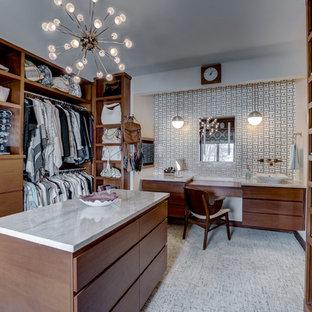 ミネアポリスの大きい男女兼用ミッドセンチュリースタイルのおしゃれなウォークインクローゼット (フラットパネル扉のキャビネット、中間色木目調キャビネット、カーペット敷き、グレーの床) の写真