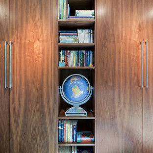 Inspiration for a mid-sized midcentury women's built-in wardrobe in Indianapolis with flat-panel cabinets and medium wood cabinets.